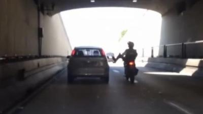 Un motard mécontent veut mettre un coup de pied dans une voiture mais il se ramasse par terre