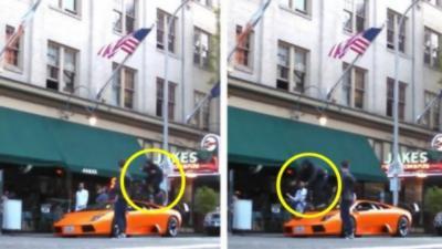 Il roule en vélo sur une Lamborghini Murcielago stationnée devant un restaurant