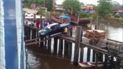 Au Brésil, on embarque une voiture sur un ferry en roulant sur des vulgaires planches en bois