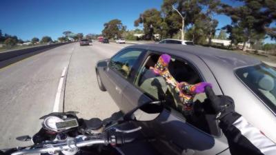 Un motard attrape des pieds qui dépasse d'une fenêtre de voiture