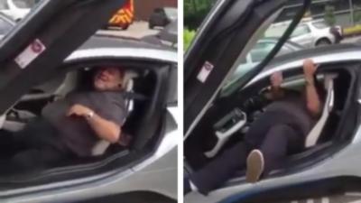 Un homme en surpoids n'arrive pas à sortir de sa BMW i8