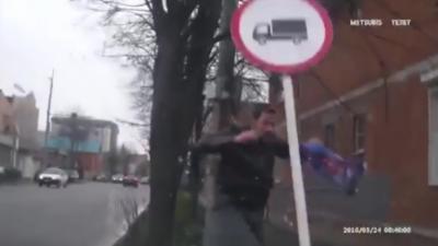 Un piéton se prend un méchant KO par un panneau de signalisation