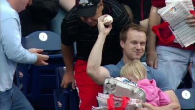 Il attrape une balle de Baseball sans bouger avec sa fille dans les bras