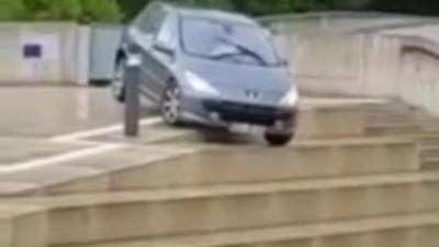 Une femme passe par les escaliers avec sa voiture pour échapper aux innondations