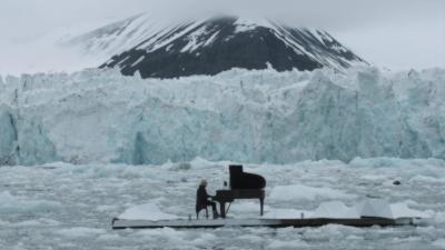Un pianiste joue dans l'Arctique pendant que les glaciers s'effondrent derrière lui