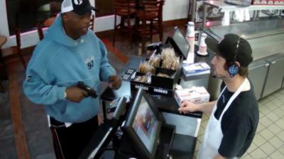 La caissier d'un fast food hyper calme alors qu'un cambrioleur pointe une arme sur lui