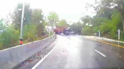 Un homme en scooter évite miraculeusement un camion qui se renverse et qui lui fonce dessus