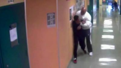 Un employé d'une école soulève un étudiant du sol en le prenant par le cou