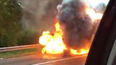 Un voiture en feu explose juste au moment où il passe à côté d'elle en filmant