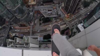 Un cascadeur russe s'amuse avec un skate sur le bord d'un gratte-ciel à Hong-Kong