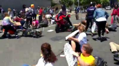 Un motard fonce et force le passage dans des manifestants qui bloquent une rue allongés sur le sol