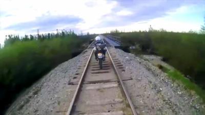 Un motard malchanceux va avoir la peur de sa vie en traversant le pont d'une ligne de chemin de fer