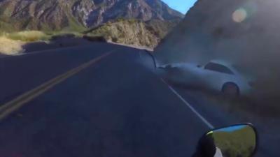 Un motard évite de justesse une voiture qui vient s'exploser contre la falaise