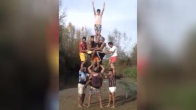 Un homme porte 10 personnes pour réaliser une pyramide humaine