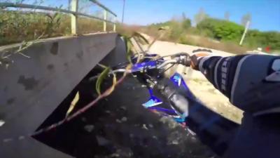Un motard roule à toute vitesse sur un chemin et tombe dans un canal