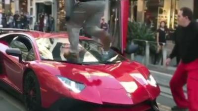 Un mec court sur une Lamborghini Aventador SuperVeloce