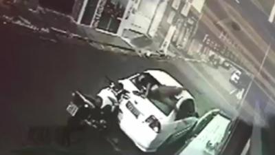 Un motard sans casque traverse la lunette arrière d'une voiture
