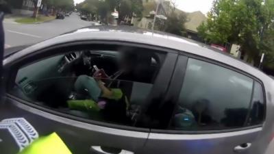 Une femme concentrée sur son téléphone ne remarque même pas le policier qui l'interpelle