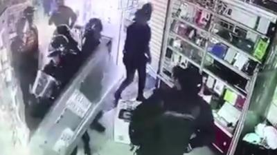 La police anti-émeutes surprise par une caméra en train de voler dans un magasin