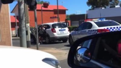 Un policier tellement occupé à donner des coups de matraque qu'il ne remarque pas qu'un suspect prend la fuite