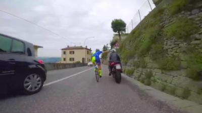 Un cycliste en pignon fixe s'amuse à suivre une moto dans une descente de montagne