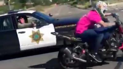 Un policier sort son arme pour un motard qui fait un wheeling sur la route