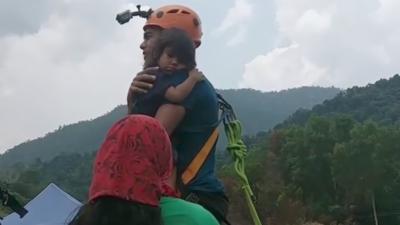 Il fait un saut pendulaire avec sa fille de 2 ans qu'il tient seulement dans les bras