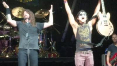 Une personne du public monte sur scène et met le feu pendant un concert des Foo Fighters