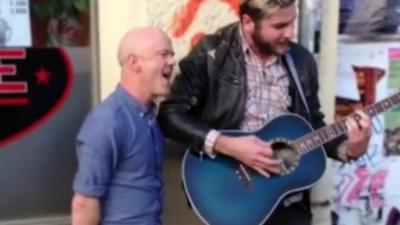 Le chanteur Jimmy Somerville accompagne un artiste de rue qui chante sa chanson