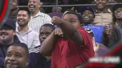 Battle de danse entre un enfant et un membre de la sécurité pendant la Dance Cam à la mi-temps d'un match de basket