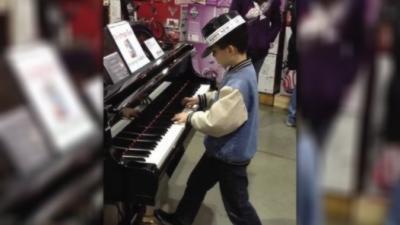 Un jeune garçon joue du piano comme personne dans un magasin