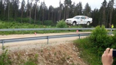 Une BMW M3 fait un énorme saut pendant un rallye