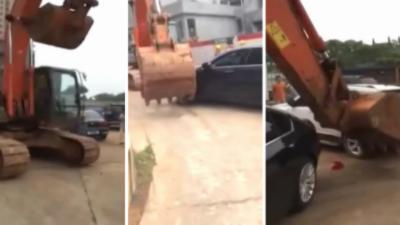 Une pelleteuse pousse des voitures qui gênent la ciculation