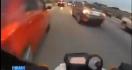 Un motard fonce entre les voitures dans un bouchon