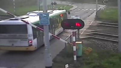 Un chauffeur de bus passe de force un passage à niveau alors qu'un train arrive
