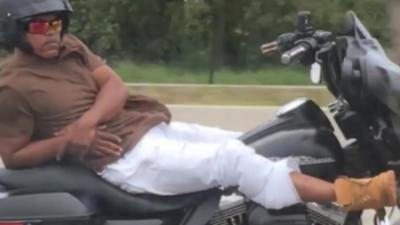 Un motard roule allongé sur sa Harley-Davidson sur une autoroute