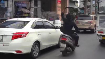 Un vietnamien en scooter casse tous les rétroviseurs qu'il croise avec une machette