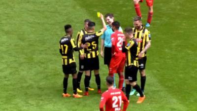 Un arbitre de football se prend un carton jaune de la part d'un joueur