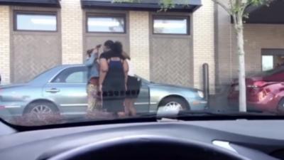 Une femme pointe une arme sur la tempe d'une autre femme dans la file d'un drive