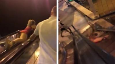 Une femme glisse sur la rambarde d'un escalator et tombe