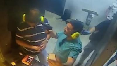 Un idiot pointe une arme chargée sur la tête de son pote pour faire une photo dans un stand de tir