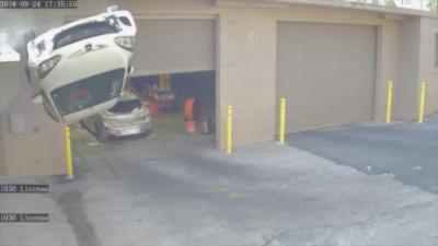 Une voiture atterrit sur le toit devant un garage