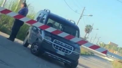 Un automobiliste bloqué à un passage à niveau fait coucou au train pour l'arrêter