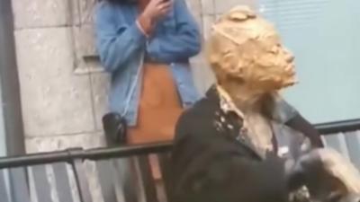Une femme se recouvre le visage avec du beurre de cacahuète en pleine rue