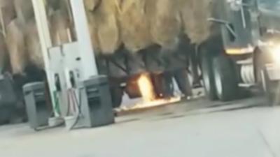 Un homme fait de la soudure sur son camion chargé de foin dans une station essence