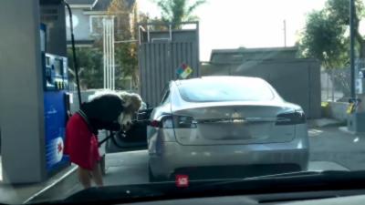 Une blonde essaye de faire le plein de sa Tesla dans une station-service