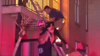 Des pompiers jettent des enfants dans un appartement en feu