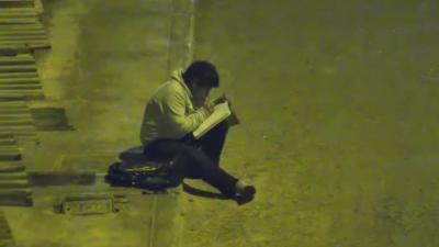 Un enfant fait ses devoirs dehors parce que sa maison n'a pas l'électricité