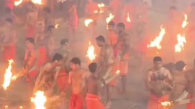 Ils se balancent des torches enflammées pour apaiser une déesse