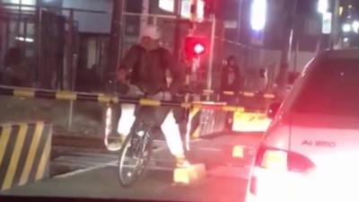 Un cycliste attend du mauvais côté de la barrière alors qu'un train arrive
